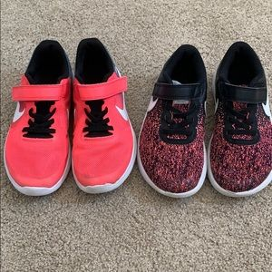 TWO pairs of girls Nike sneakers.